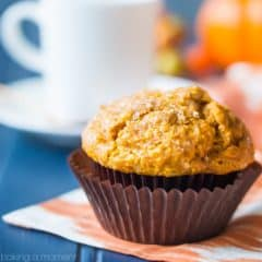 Pumpkin muffin with dark brown liner, sitting on an orange cloth on a blue tabletop. White coffee cup and mini pumpkins in the background.