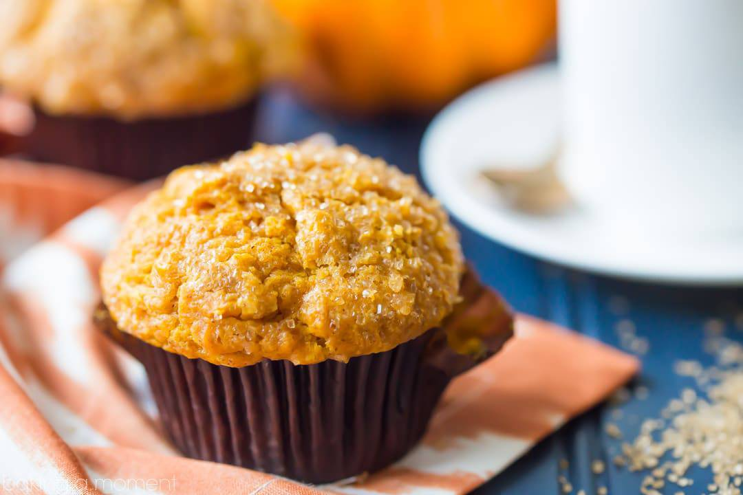 Pumpkin muffin on an orange cloth and blue tabletop, with coffee cup, mini-pumpkin, and coarse sugar in the background.