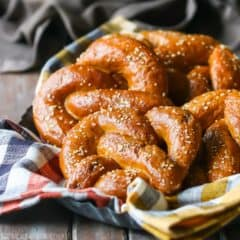 Abundant basket full of burnished brown soft pretzels, nestled into an orange plaid napkin.