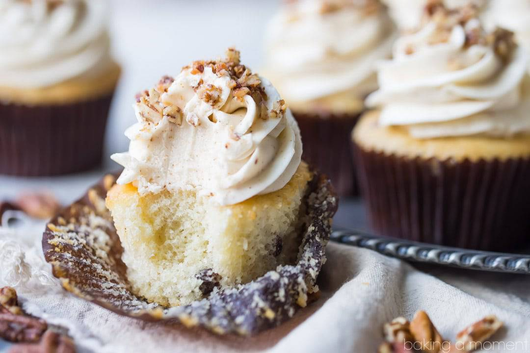 Five butter pecan cupcakes topped with swirls of brown butter frosting and sprinkled with pecans, on an antique silver platter.