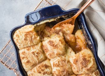Snickerdoodle Apple Cobbler in a dark blue casserole dish: apple pie filling topped with cinnamon sugar snickerdoodle cookies, on a gray background with a copper serving spoon.