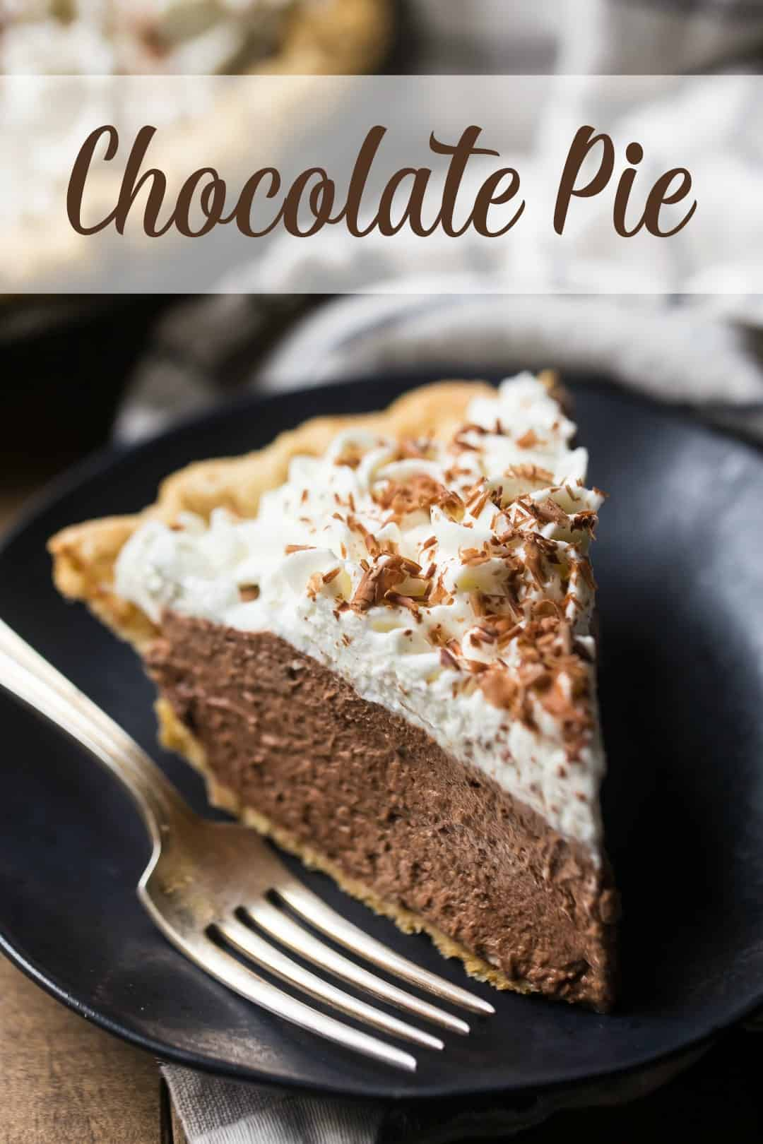 "Close up image of a slice of chocolate pie on a dark plate with a silver fork, and a text overlay above reading ""Chocolate Pie."""