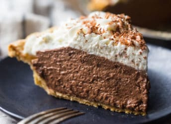 A tall slice of chocolate pie with whipped cream on a dark blue plate.