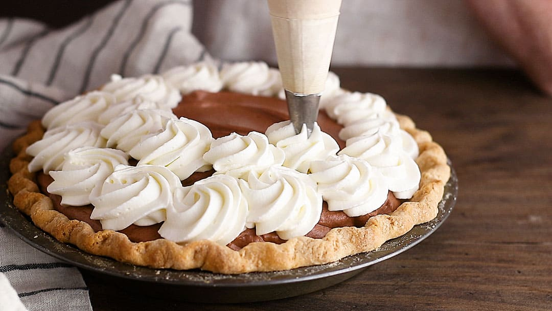 Piping rosettes of whipped cream on a chocolate pie.