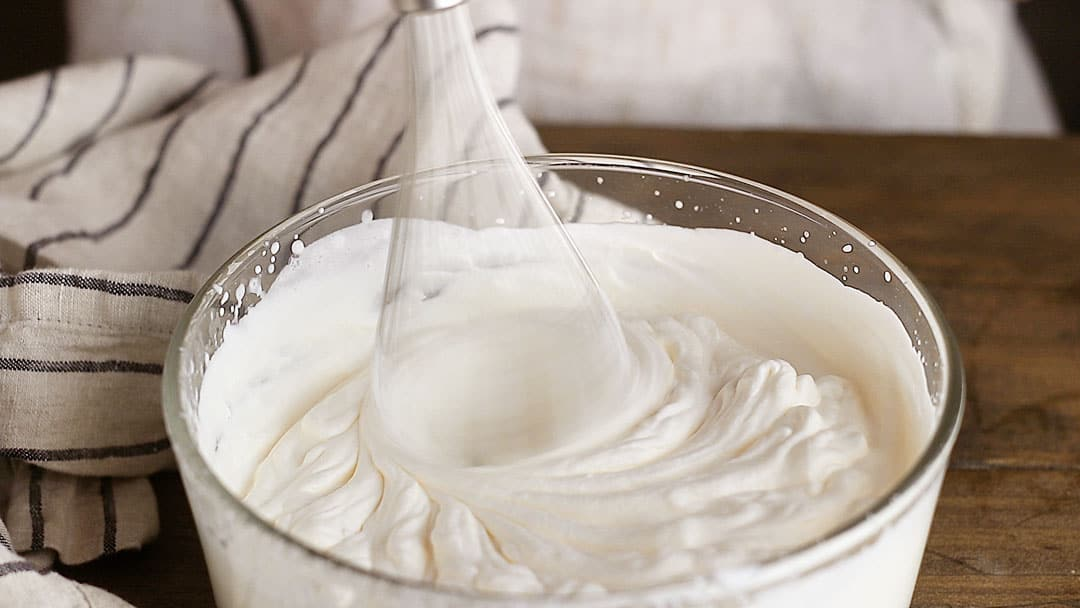 Whipping cream in a glass bowl with an electric mixer.