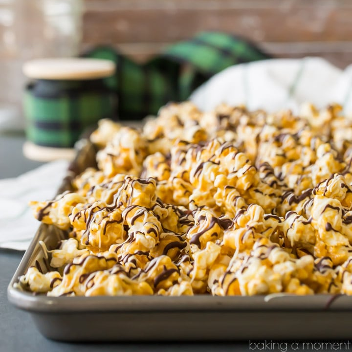 Homemade Moose Munch butter toffee caramel popcorn with nuts and chocolate drizzle, on a baking sheet with a spool of holiday ribbon in the background
