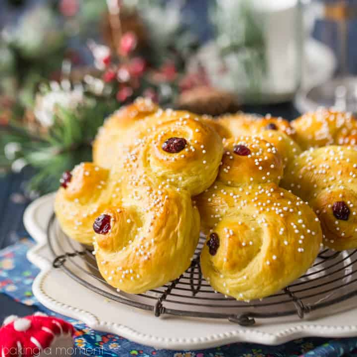 "Saffron yellow St. Lucia Buns in an ""S"" shape, sprinkled with sugar and garnished with dried cranberries, on a cooling rack with a dark blue background with Christmas decorations."
