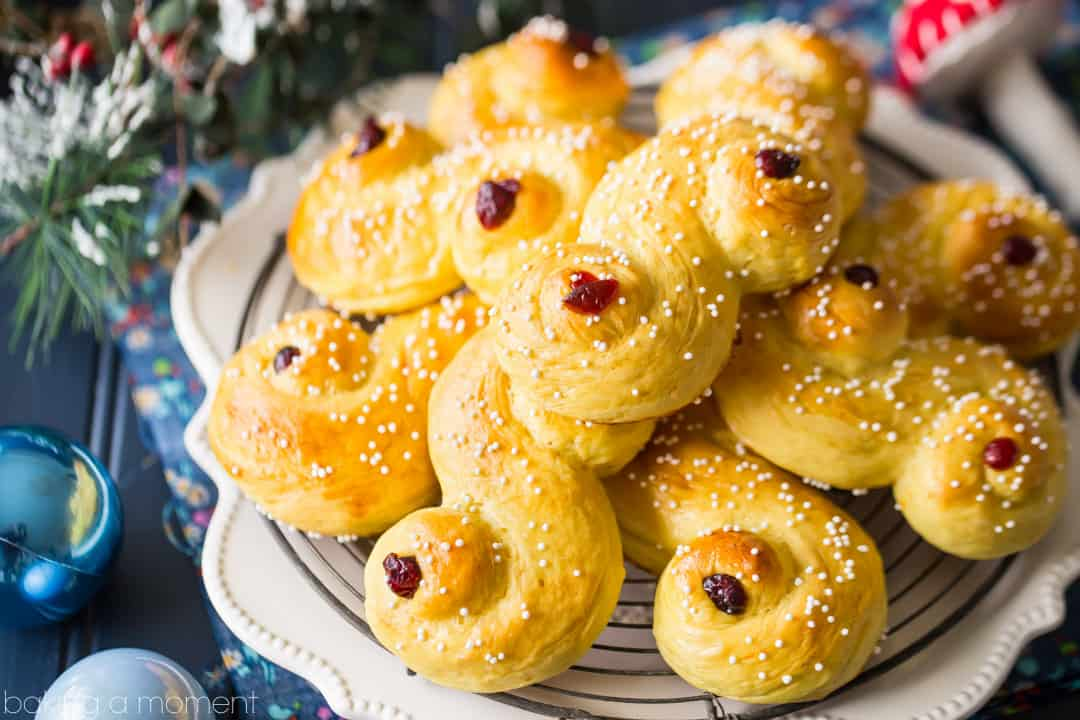 Saffron-scented Lucia Buns, sprinkled with sugar and garnished with dried cranberries. A centuries old Scandanavian tradition- so light and soft, and perfect with a cup of coffee! #food #bread #desserts #baking #swedish #luciabuns #stluciaday #holiday