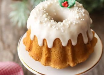 Mini brown sugar pound cake bundt on a white stand with white icing, white sprinkles, and a sprig of royal icing holly leaves & berries, with holiday greenery and a red checked napkin in the background.
