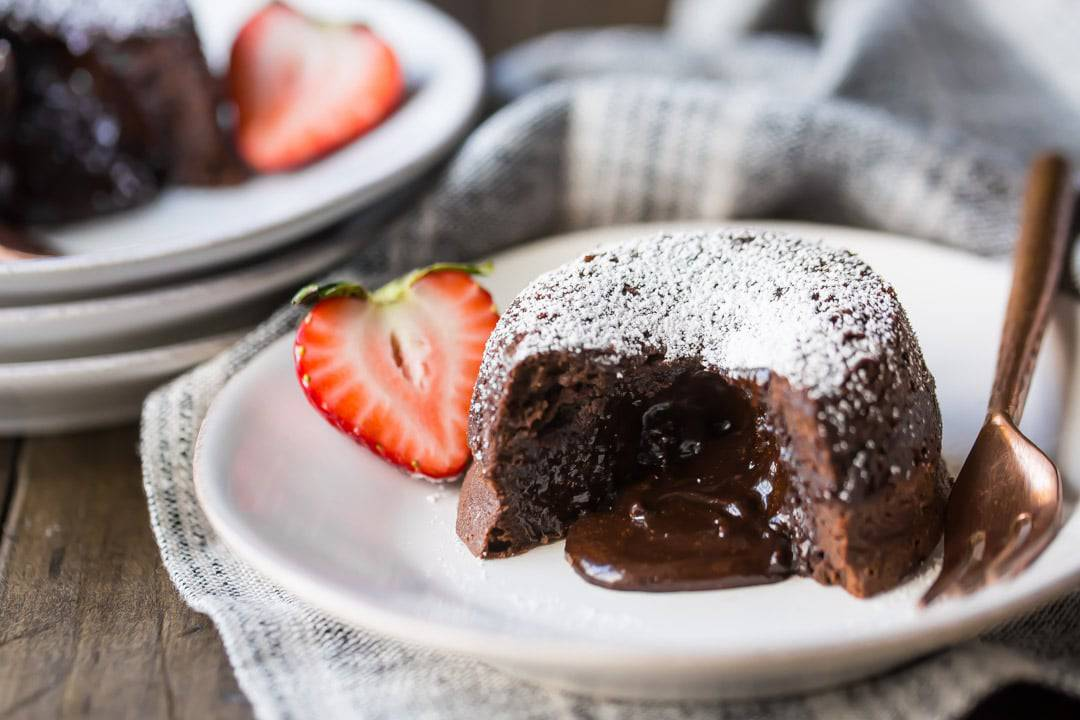 Chocolate Molten Lava Cake on a white plate, with liquid chocolate spilling from the center. Garnished with a strawberry, and a linen cloth beneath the plate and a copper fork on the side.