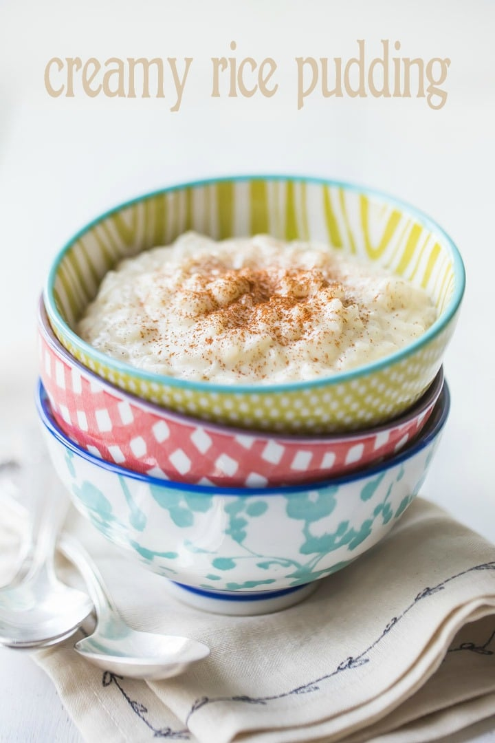 Three colorful bowls stacked on a linen napkin, filled with a creamy rice pudding and sprinkled with cinnamon.