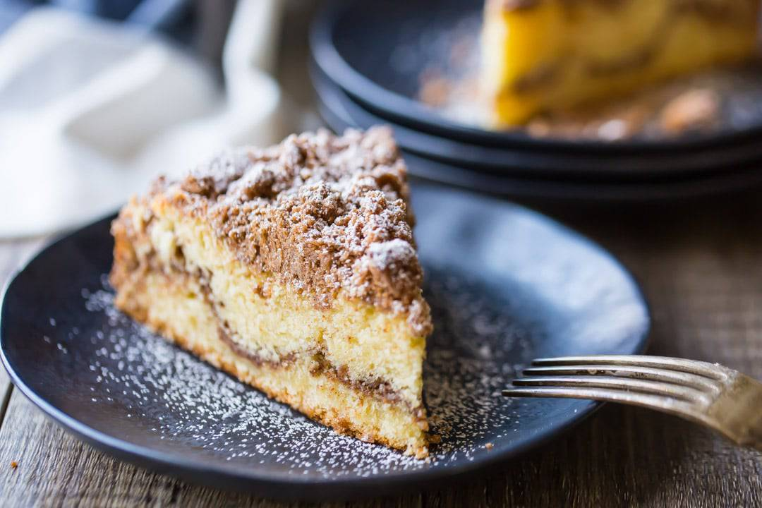 A thick slice of cinnamon crumb cake, ribboned with cinnamon streusel & topped with a thick layer of crumbly streusel, on a dark blue plate dusted with powdered sugar.