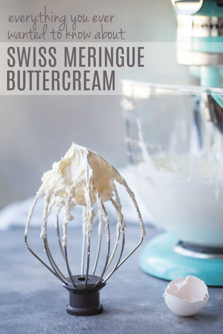 Whisk attachment with Swiss meringue buttercream and blue mixer in background with broken eggshells off to one side.