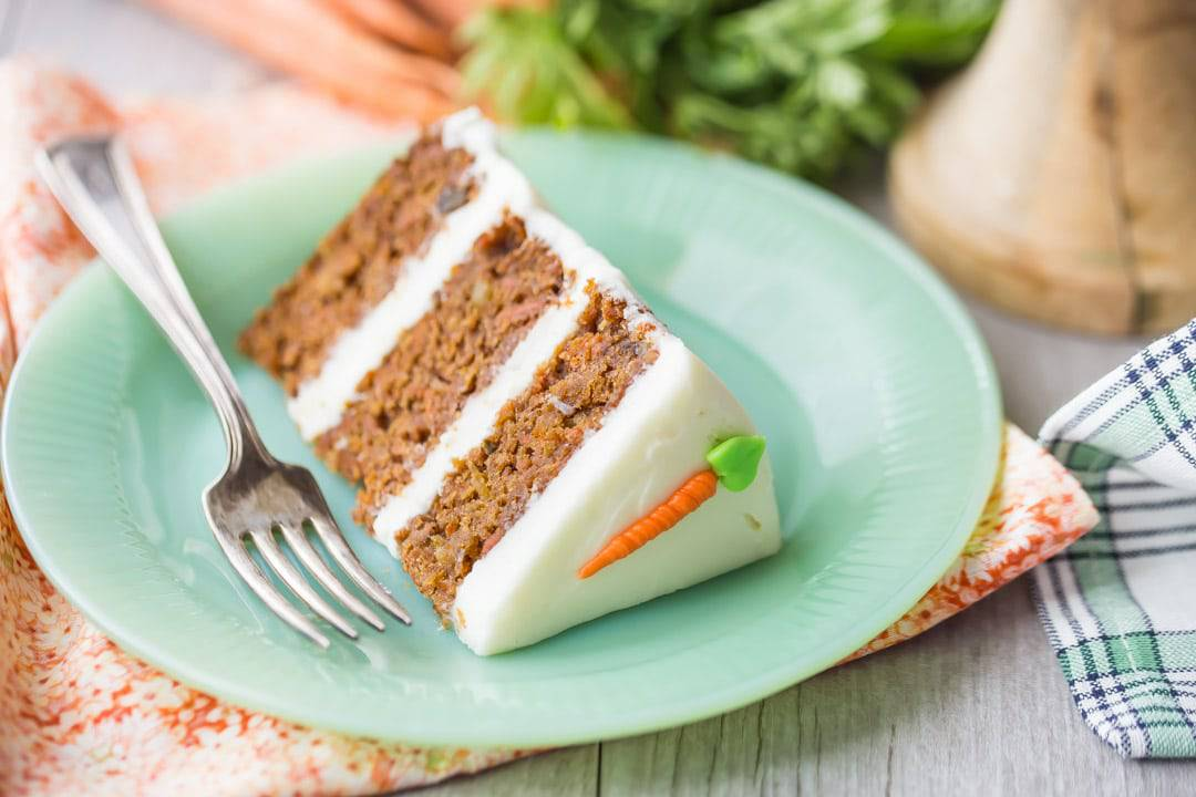 Slice of triple-layer carrot cake with cream cheese frosting, on a green plate with fresh carrots in the background.