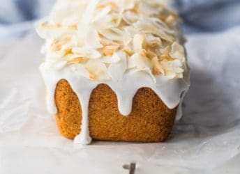 A loaf of glazed coconut bread with dripping icing and toasted coconut flakes on top, on a marble board with a blue cloth underneath.