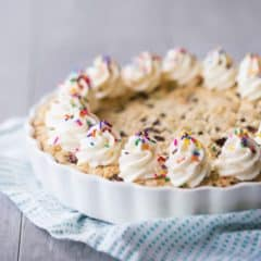 Square image of a giant chocolate chip cookie cake with vanilla buttercream rosettes and rainbow sprinkles, with a turquoise cloth on a gray background.
