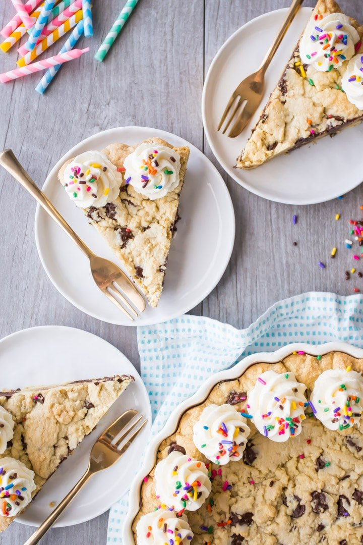 Vertical overhead image of slices of chocolate chip cookie cake on plates with gold forks and rainbow sprinkles.