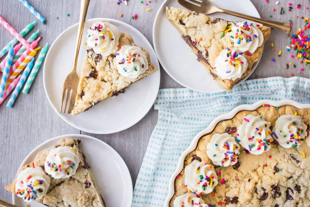 Horizontal overhead image of slices of chocolate chip cookie cake on plates with gold forks and rainbow sprinkles.