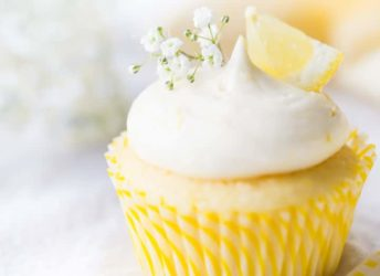 Lemon cupcake with lemon curd filling & lemon cream cheese frosting, garnished with baby's breath and a wedge of fresh lemon.