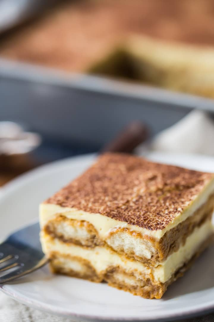 Vertical image of 2 slices of tiramisu, plated and with the pan of tiramisu in the background.