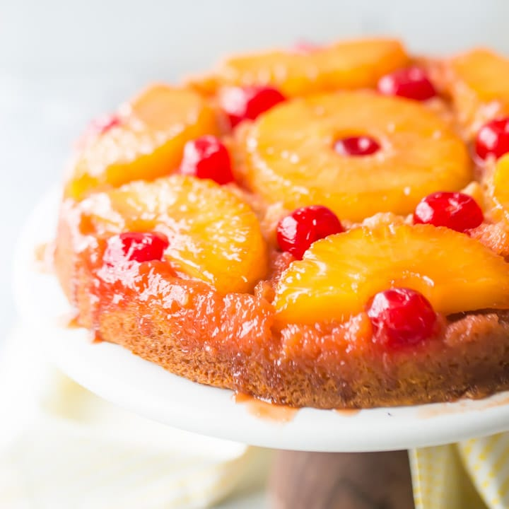 Square Image of a pineapple upside down cake with cherries on a white cake stand.