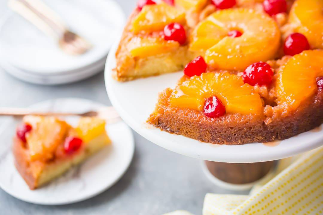 Horizontal image of a pineapple upside down cake on a white stand with a slice cut out and placed on a plate in the background.