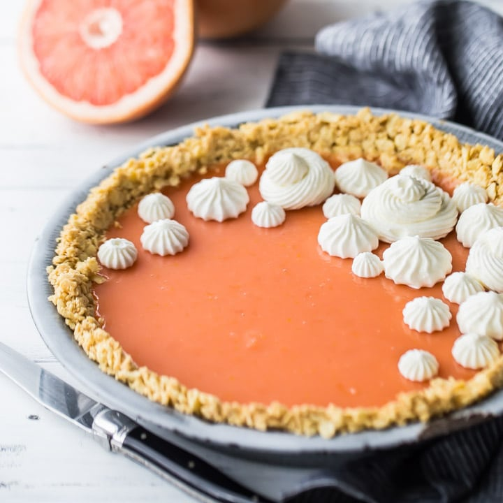 Square image of Paloma cocktail (grapefruit tequila) pie with Saltine cracker crust, on a white background with fresh grapefruit in the background.