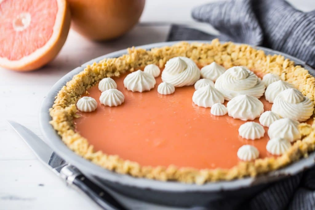 Horizontal image of Paloma cocktail (grapefruit tequila) pie on a white background with fresh grapefruit in the background.