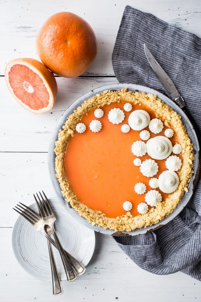Vertical overhead image of Paloma cocktail (grapefruit tequila) pie on a white background with fresh grapefruit, plates, and forks.