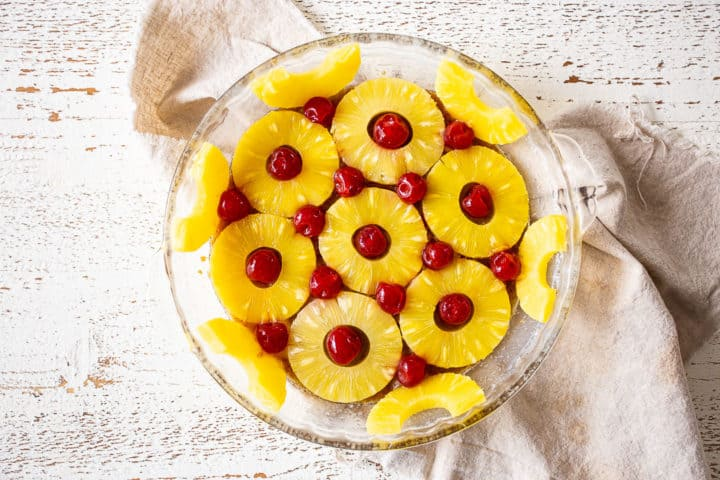 Arranging pineapple slices and cherries in a pattern at the bottom of a cake pan.
