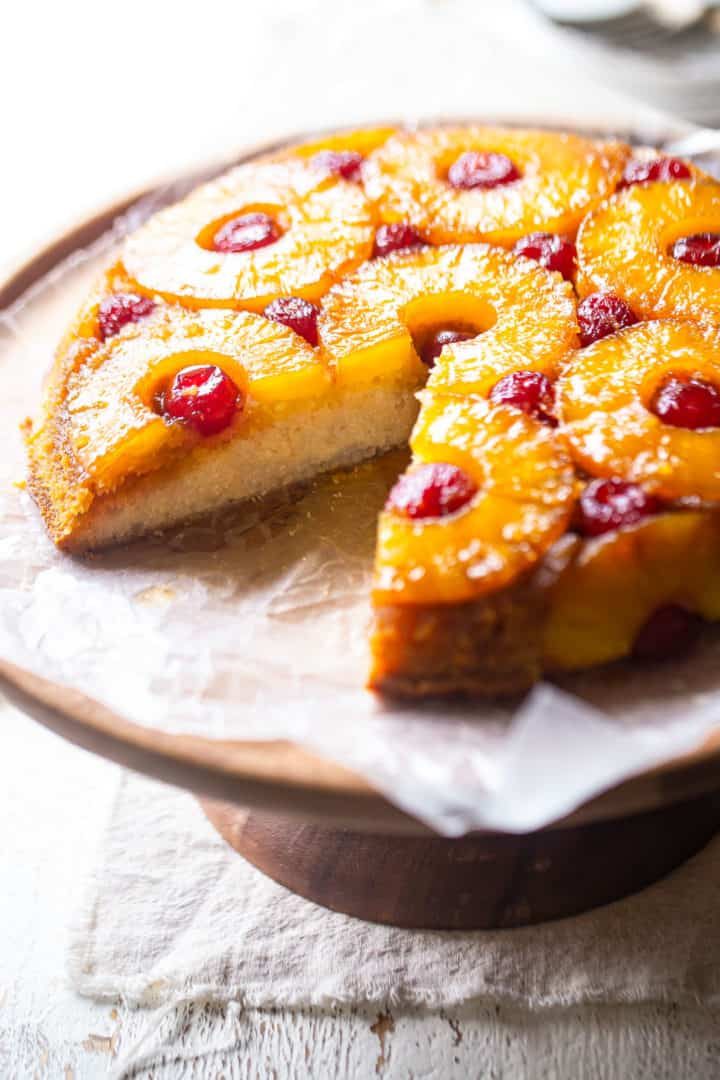 How to make pineapple upside-down cake, served on a cake stand with a linen napkin.