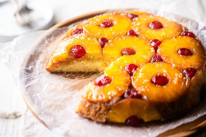 Pineapple upside-down cake from scratch, with one slice removed, showing the soft, moist interior.