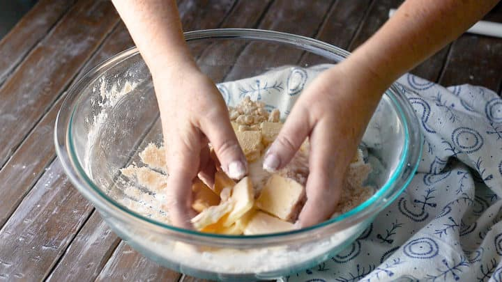 Tossing slices of butter in dry ingredients to coat them.