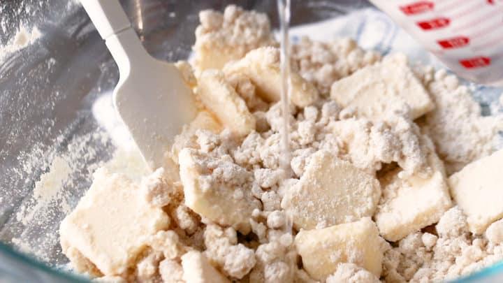 Adding ice water to homemade pie crust recipe.