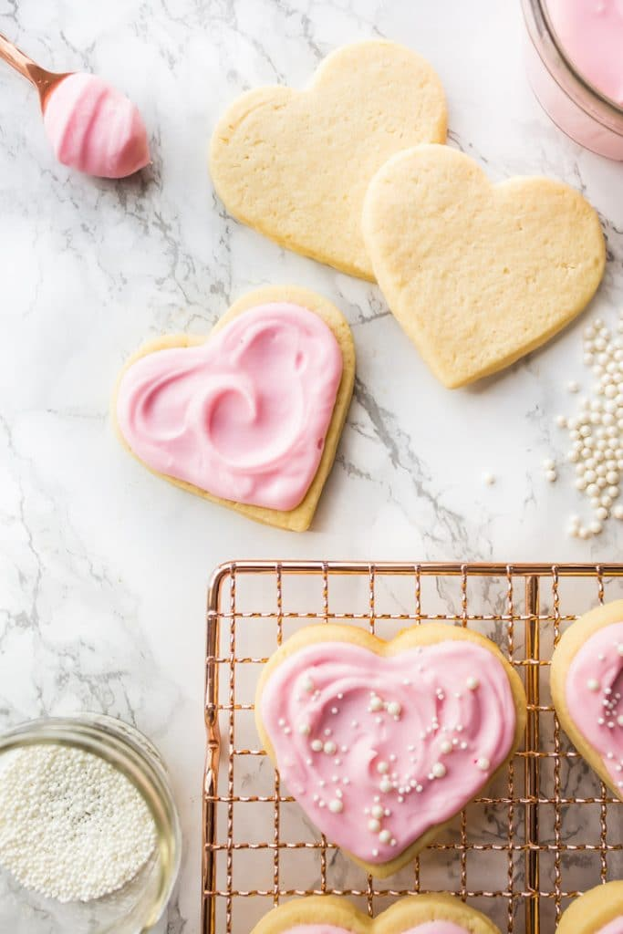 Vertical image of heart-shaped cream cheese cut-out sugar cookies on a copper cooling rack with pink sugar cookie frosting.