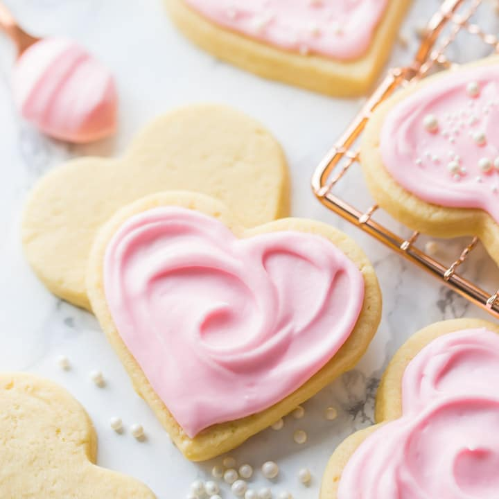 Square image of a heart-shaped soft cut-out sugar cookie with pink sour cream icing.