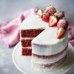 Moist triple-layer red velvet cake with cream cheese frosting and fresh strawberries.