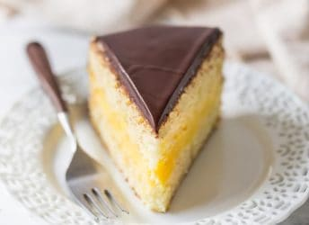 Slice of Boston Cream Pie with moist vanilla cake sandwiched around rich pastry cream filling, and a shiny chocolate glaze topping.