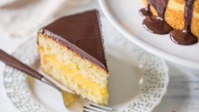 Perfect slice of Boston Cream Pie on a plate next to the full cake, showing ganache topping dripping down the sides.
