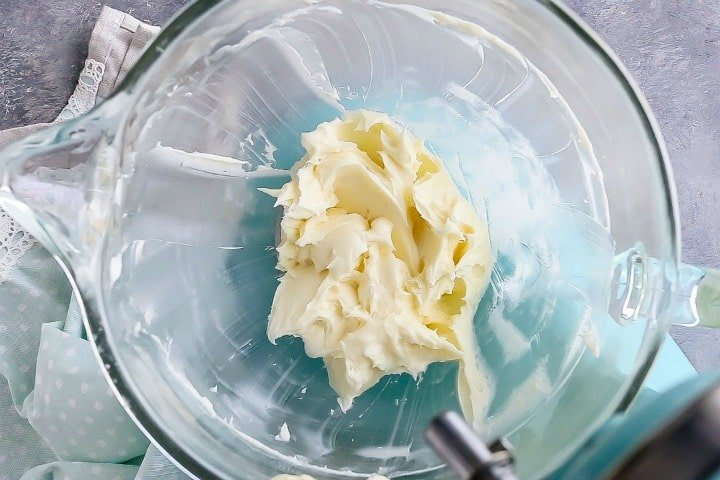 Whipped cream cheese frosting in a glass mixing bowl.