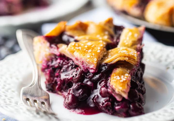 A slice of blueberry pie with thick filling and a lattice top crust, presented on a lacy white plate.