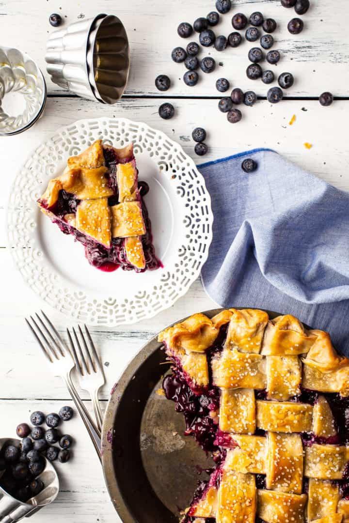 Imagen aérea de una tarta de arándanos con una rebanada cortada y plateada, con el relleno grueso de la tarta de arándanos derramándose.