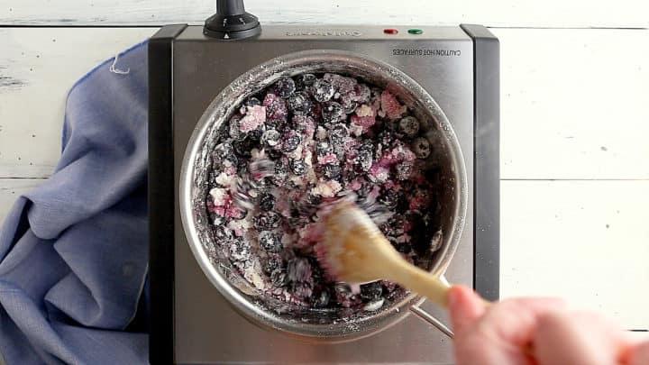 Mezclar arándanos con azúcar, maicena y sal para hacer un relleno de tarta de arándanos.