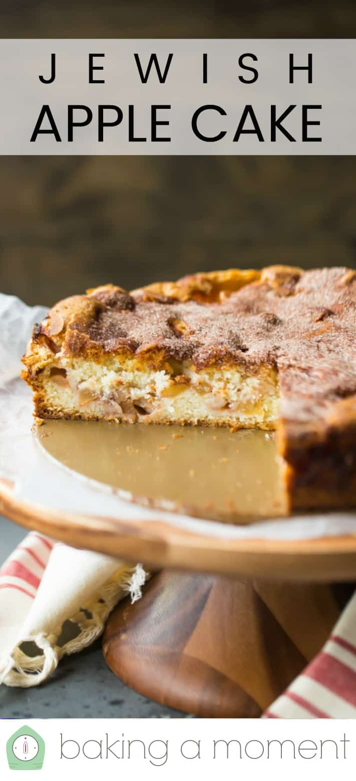 """Close-up image of a homemade Jewish apple cake with cinnamon sugar on a wooden cake stand, with a text overlay above that reads """"Jewish Apple Cake."""""""