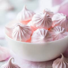 Pale pink meringue kisses in a white bowl.