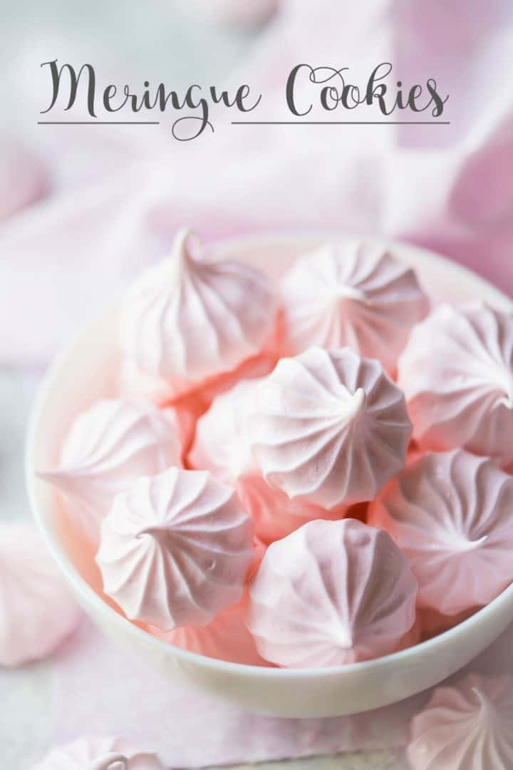 "Bowl full of pastel pink meringue kisses on a white background with text overlay reading ""Meringue Cookies."""