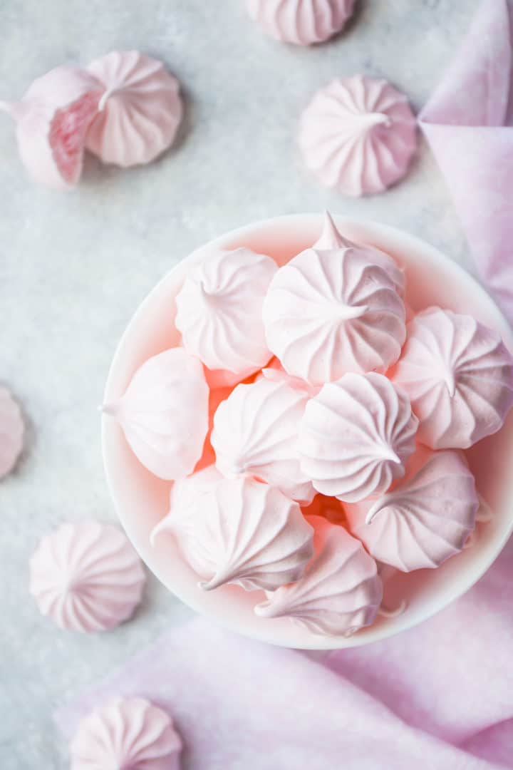 Overhead image of baby pink meringue cookies in a white bowl with a pink cloth.