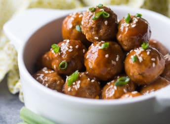 Glazed sweet & sour meatballs in a white crock with scallions.