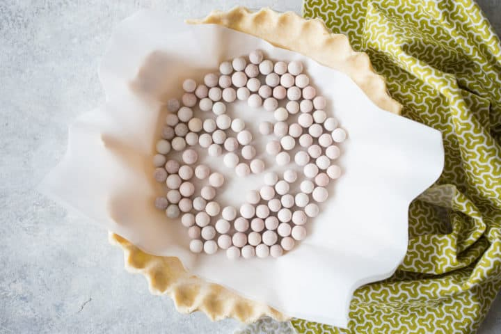 Blind-baking pie crust with parchment and ceramic pie weights.