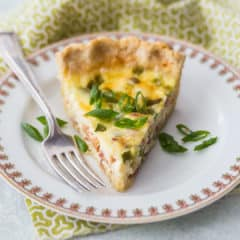 A slice of quiche Lorraine on a china plate with a green printed napkin.